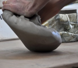 Kneading clay as part of the preparation before throwing...