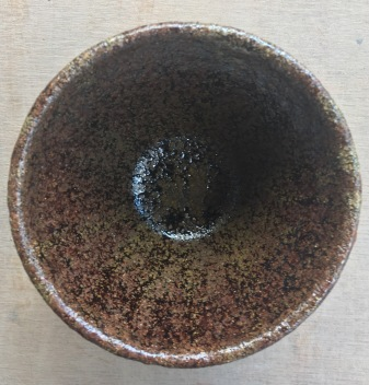 A tumbler fired to stoneware temperatures with draff ash and rock dusts