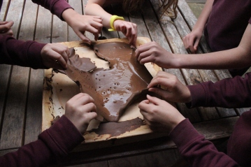 Year 5 children preparing clay they dug the previous week